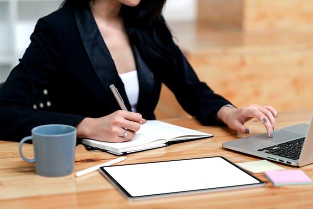 Donna di affari del primo piano che lavora con il computer portatile e che prende appunti all'ufficio.