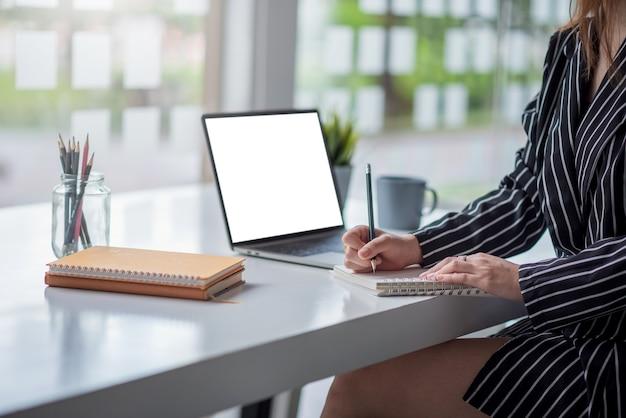 Avvicinamento. imprenditrice scrivendo su un taccuino in bianco sul tavolo in ufficio. schermo bianco vuoto.