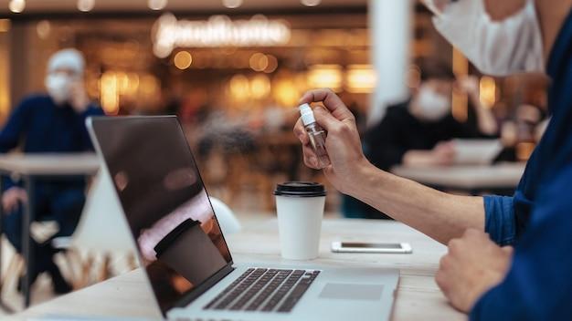 Avvicinamento . visitatore del caffè che spruzza antisettico sul suo laptop. foto con copia-spazio