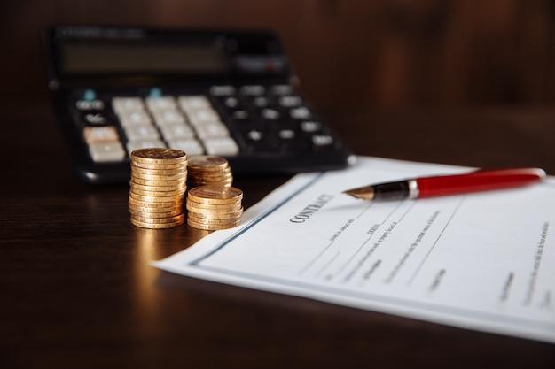 Close-up di calcolatrice e penna, firma ufficiale del contratto.