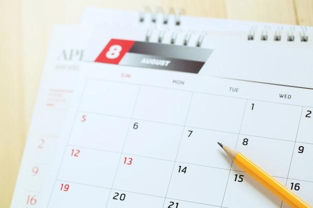 Primo piano numero di pagina del calendario mese di agosto. matita gialla per segnare la data desiderata per ricordare la memoria sul tavolo.