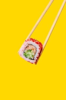 Primo piano california roll con salmone e cetriolo sulle bacchette su sfondo giallo.