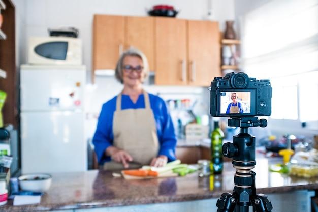 Primo piano della telecamera che riprende una donna matura o una donna anziana che cucina e fa dal vivo o video per i suoi social network e media - registrazione dello stile di vita dell'influencer a casa in cucina per pubblicare le sue ricette
