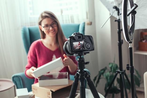 Schermo della fotocamera in primo piano, blogger donna fa video di disimballaggio