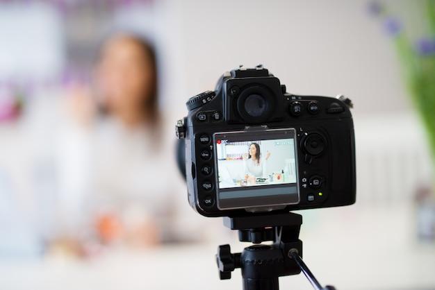 Primo piano di una fotocamera per scattare foto della giovane bella ragazza carina che è seduto al tavolo della cucina con un computer portatile su di esso e mostrando profumi e cosmetici alla fotocamera mentre sorride.
