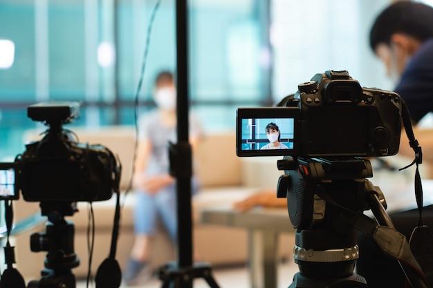 Chiuda sulla macchina fotografica sul video blog della registrazione del treppiede nelle riprese dello studio con protezione d'uso della maschera di protezione della giovane donna asiatica in schermo.