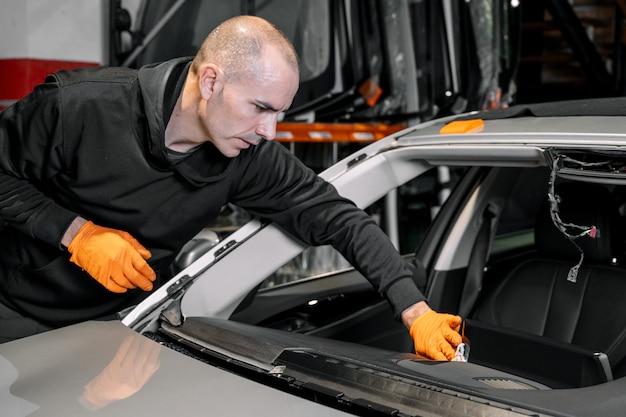 Primo piano, vetri per auto, fissaggio e riparazione di un parabrezza. processo di sostituzione del parabrezza di un'auto in un garage. pulizia di un cruscotto.