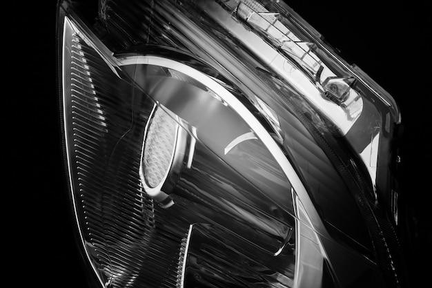 Primo piano delle luci dell'auto su uno sfondo nero isolato. faro dell'auto tagliato