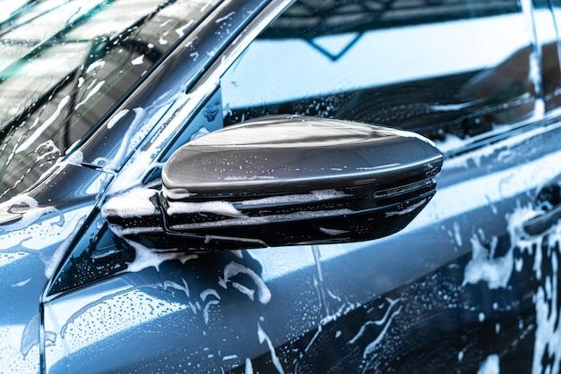 Primo piano specchietto laterale auto con schiuma lavaggio auto