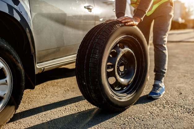 Primo piano di una gomma di automobile. l'autista dovrebbe sostituire la vecchia ruota con una di scorta.