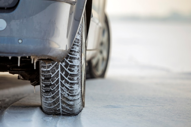 Primo piano di un pneumatico per auto parcheggiato su strada innevata durante la giornata invernale. trasporto e concetto di sicurezza.