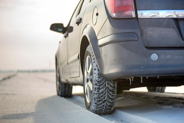 Chiuda in su di una gomma di automobile parcheggiata sulla strada nevosa il giorno di inverno. concetto di trasporto e sicurezza.