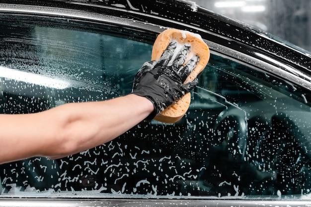 Chiuda in su del lavoratore dell'autolavaggio che indossa guanti protettivi e lava il finestrino dell'auto con una spugna saponosa