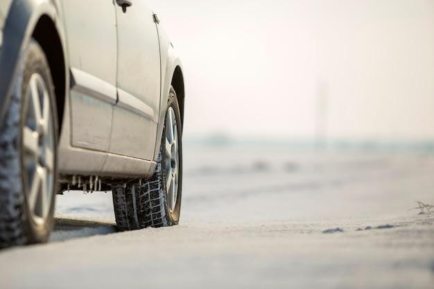 Primo piano del pneumatico di gomma delle ruote di automobile nella neve profonda.