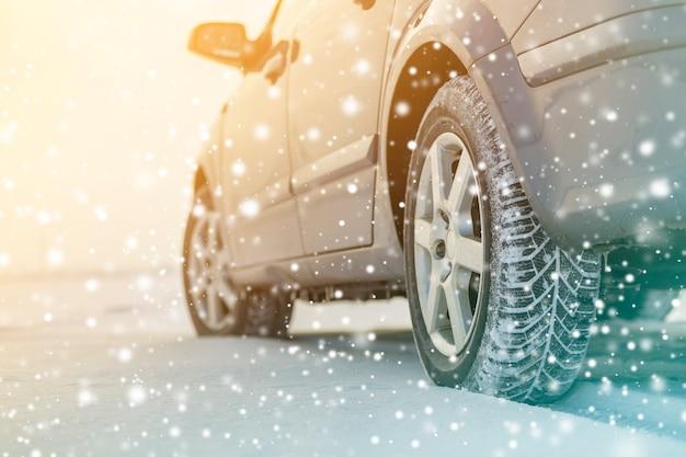 Primo piano dei pneumatici di gomma delle ruote dell'automobile nella neve profonda dell'inverno. trasporto e concetto di sicurezza.