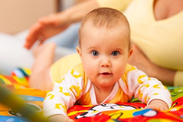 Primo piano di premurosa giovane e bella madre insegna i colori alla sua affascinante figlia di sei mesi che giace in un'accogliente camera per bambini