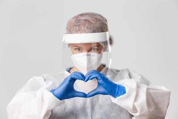 Primo piano della dottoressa premurosa e devota in dispositivi di protezione individuale che mostra il gesto del cuore a sostegno, chiedere di stare al sicuro.