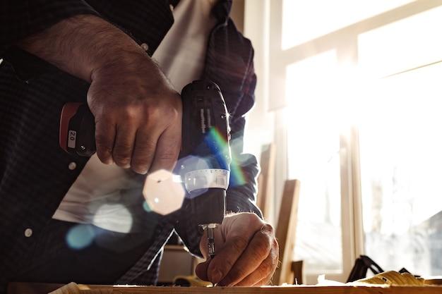 Primo piano di un falegname che pratica un foro nel legno