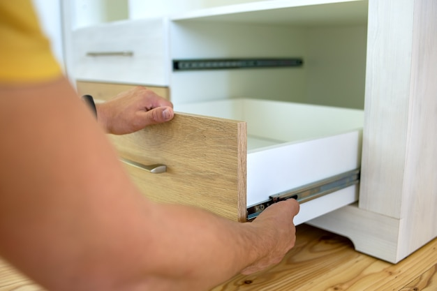 Chiuda in su delle mani del falegname che installano il cassetto di legno sui pattini scorrevoli nell'armadio contemporaneo.