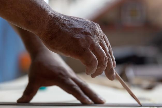 Primo piano delle mani del carpentiere che lavorano