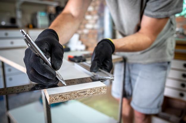 Primo piano del falegname che tiene il righello e la matita mentre fa segni sul legno al tavolo in officina.