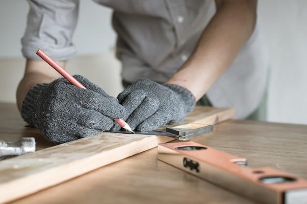 Chiuda sul legno di misura del carpentiere, giovane maschio che fa la misura sul di legno