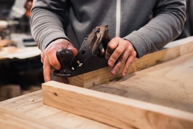 Primo piano delle mani di un falegname che pialla una doga di legno con una spazzola da falegname