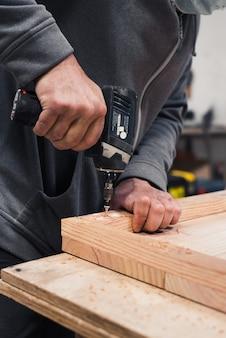 Primo piano di un carpentiere che avvita una vite con un cacciavite elettrico