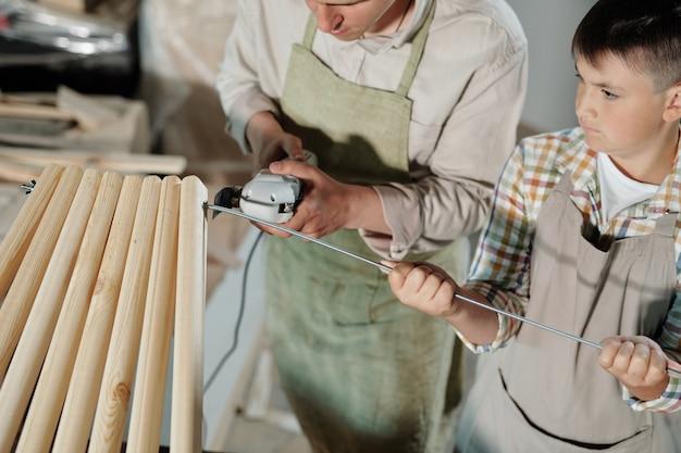 Primo piano del falegname utilizzando wen con filo di taglio durante il taglio del bastone di metallo tenuto dal figlio adolescente nel laboratorio di mobili