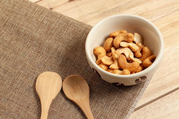 Close up anacardi arachidi cibo secco spuntino nella ciotola messo sul sacco e tavolo in legno