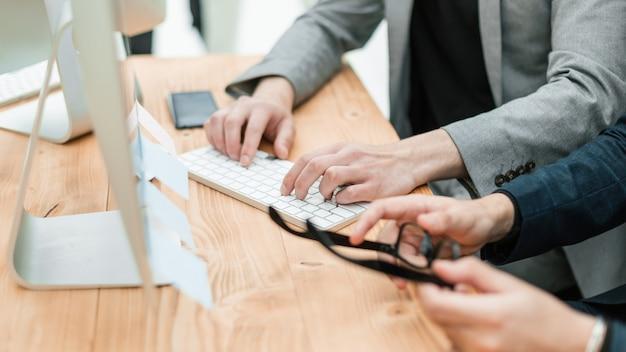Chiuda in su uomini d'affari casuali che lavorano in ufficio