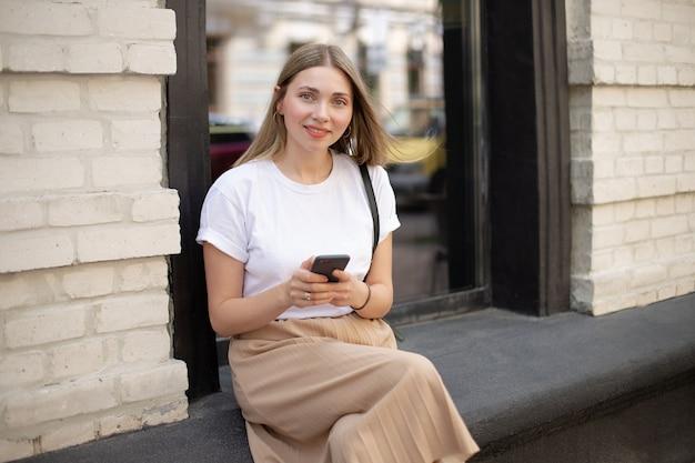 Primo piano della ragazza bionda caucasica in una t-shirt bianca utilizzando lo smartphone mentre è seduto per strada sullo sfondo di una grande finestra vicino a un edificio in mattoni