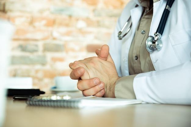 Primo piano di consulenza medica caucasica per il paziente che spiega la ricetta per il lavoro di droga nel gabinetto