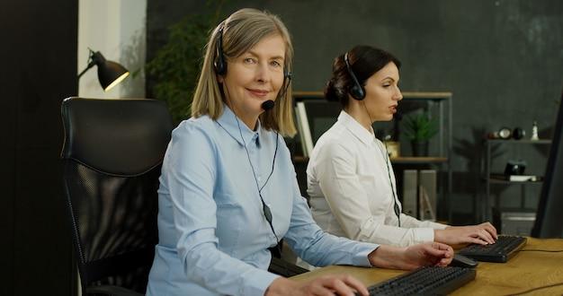 Chiuda in su della donna maggiore caucasica in cuffia avricolare che lavora nell'ufficio della call center. servizio per il concetto di clienti.