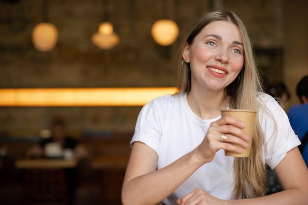 Primo piano di una donna bionda sorridente caucasica in una t-shirt bianca che guarda fuori dalla finestra e beve caffè sullo sfondo di un muro in un caffè