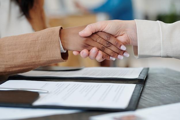 Primo piano di una donna caucasica che fa stretta di mano con una donna di colore, responsabile delle risorse umane che assume un nuovo dipendente dopo un colloquio di lavoro