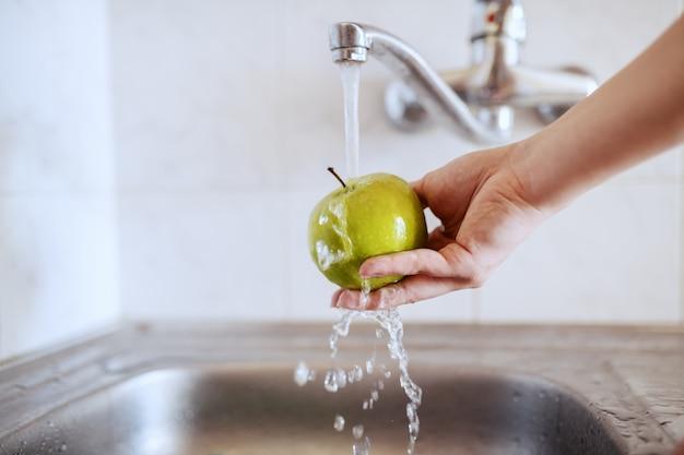 Chiuda in su della donna caucasica che lava la mela verde in lavandino.