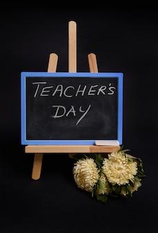 Primo piano di una lavagna di gesso con scritta festa dell'insegnante, in piedi su un cavalletto da tavolo in legno, accanto alla sveglia nera, isolata su sfondo nero con spazio per la copia.