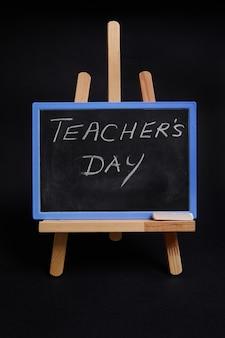 Primo piano di una lavagna su un cavalletto da tavolo in legno con scritta giornata dell'insegnante, isolata su sfondo nero con spazio per le copie.