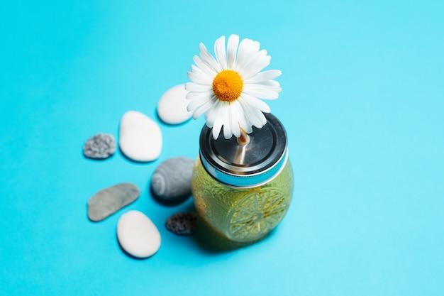 Primo piano del fiore della camomilla in paglia di fondo della tazza di vetro del succo vicino alle pietre.
