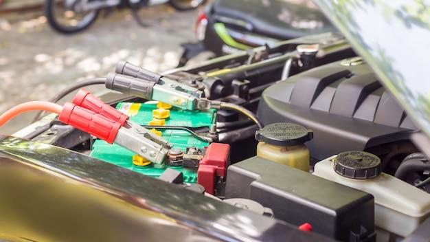 Primo piano ricarica della batteria dell'auto con l'elettricità tramite cavi jumper.