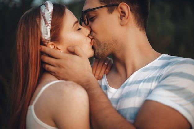 Primo piano di un'affascinante coppia che si bacia con gli occhi chiusi mentre l'uomo sta toccando il viso della sua ragazza con la mano all'aperto durante la datazione.