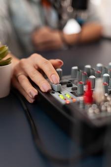 Primo piano del controllo del suono utilizzando il mixer durante il podcast online. influencer dei social media che crea contenuti professionali con attrezzature moderne e stazione di streaming internet digitale web