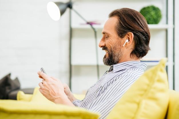 Chiuda in su dell'adulto caucasico allegro che si siede sul divano con gli auricolari wireless nelle orecchie e godendo utilizzando smartphone moderno