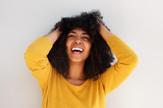 Chiuda sulla giovane donna afroamericana allegra che ride con le mani in capelli ricci