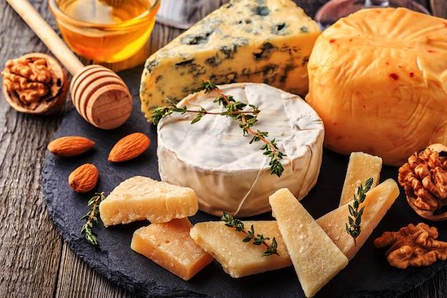 Primo piano su formaggio, noci, miele e vino rosso