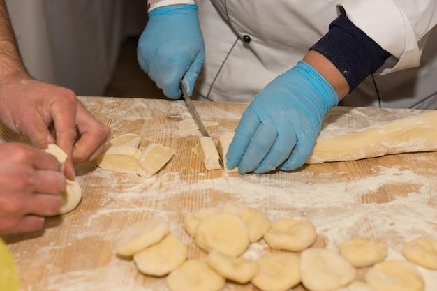 Chiuda in su dei pezzi di taglio dello chef dal rotolo di pasta