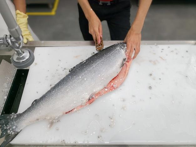 Chiuda sul pesce di taglio della mano del cuoco unico