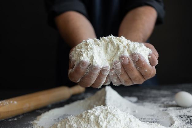 Primo piano delle mani dello chef che tengono una manciata di farina di frumento bianco, facendo la pasta