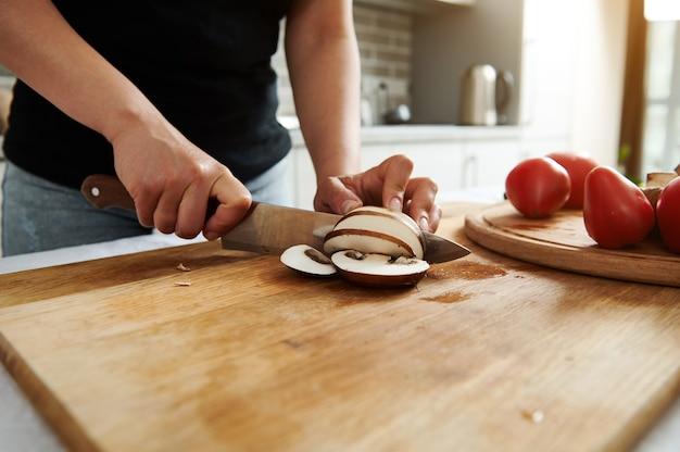 Primo piano delle mani dello chef o della casalinga mentre tagliano i funghi su una tavola da cucina in legno
